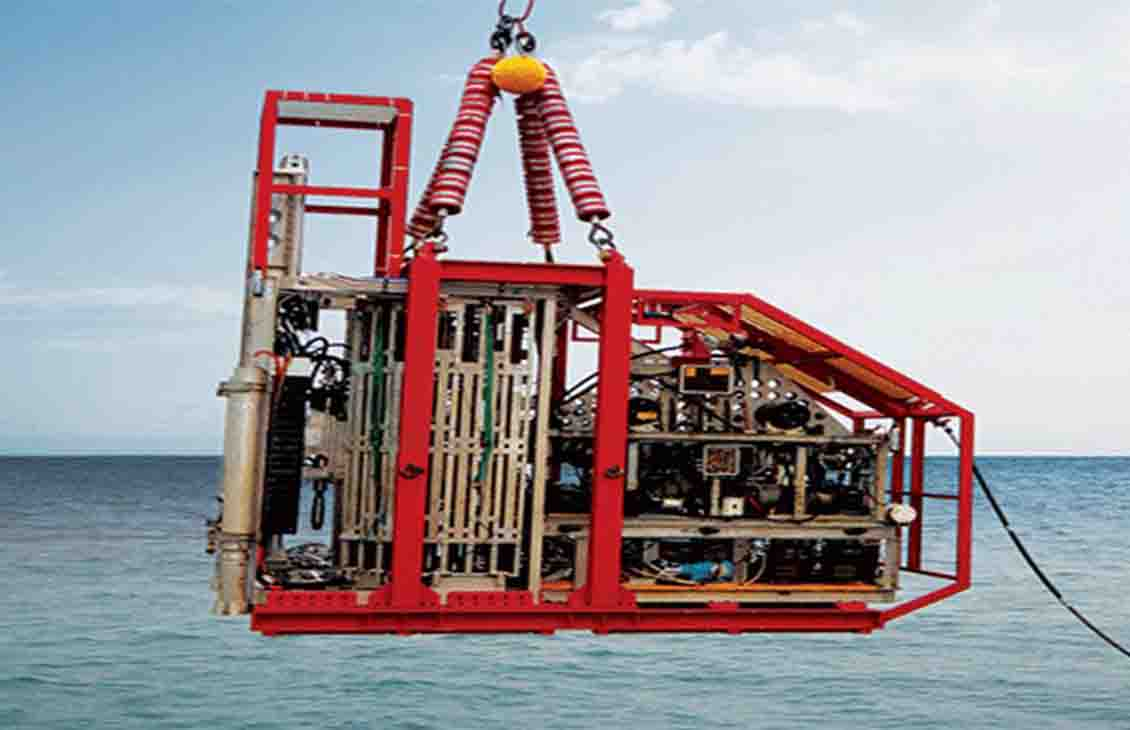 Red subsea kit being lowered into ocean.