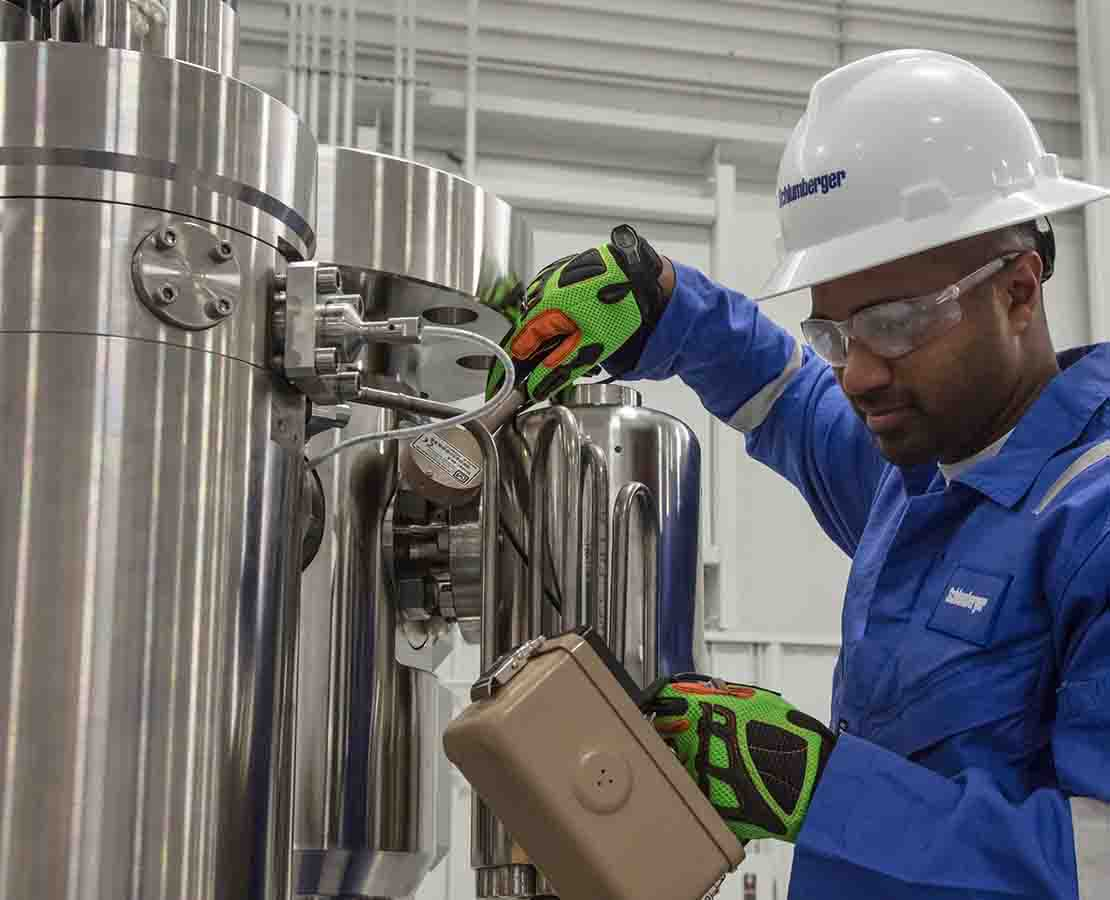 Schlumberger technician testing multiphase meter in warehouse.