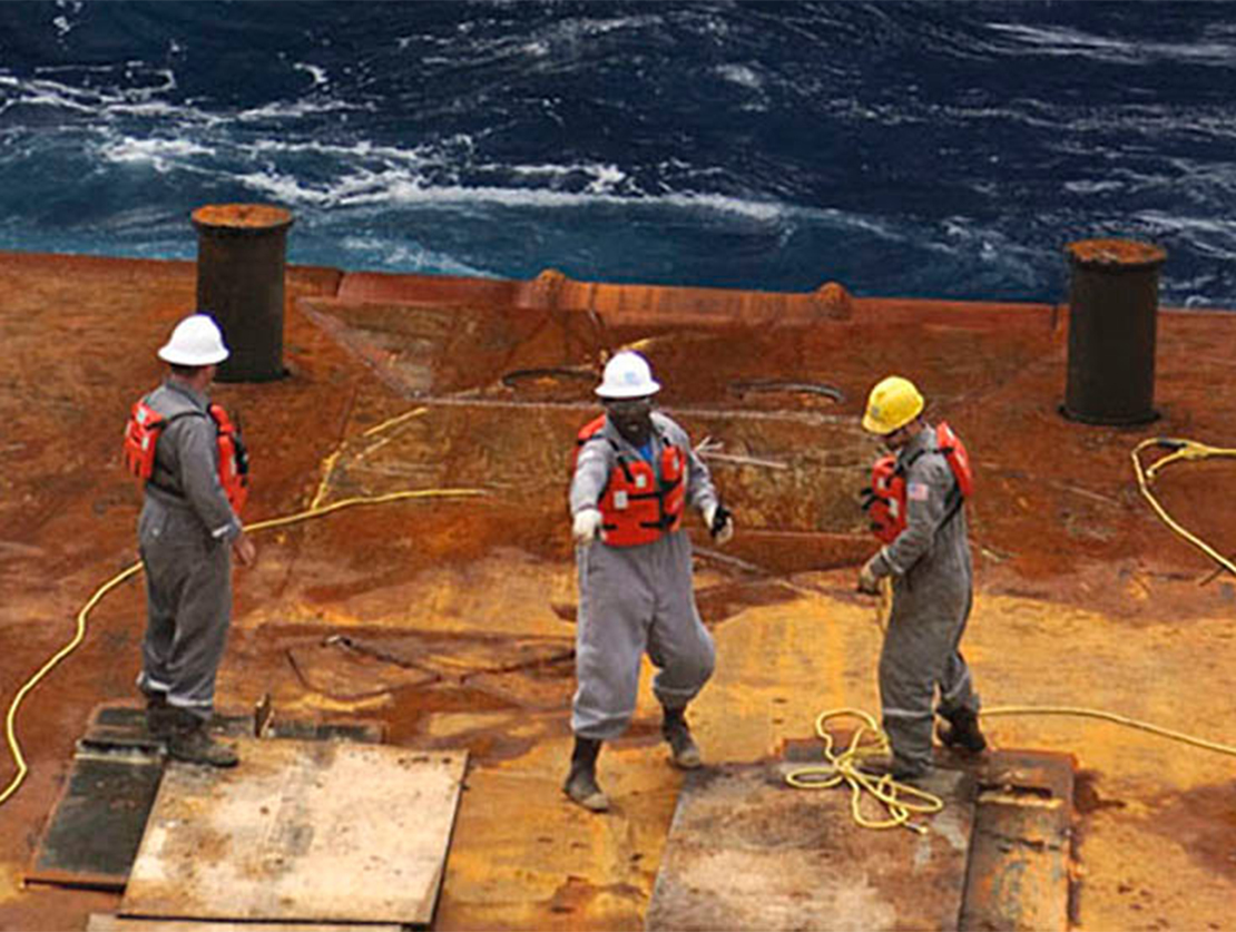 Subsea completion personnel in PPE on a deck near water.