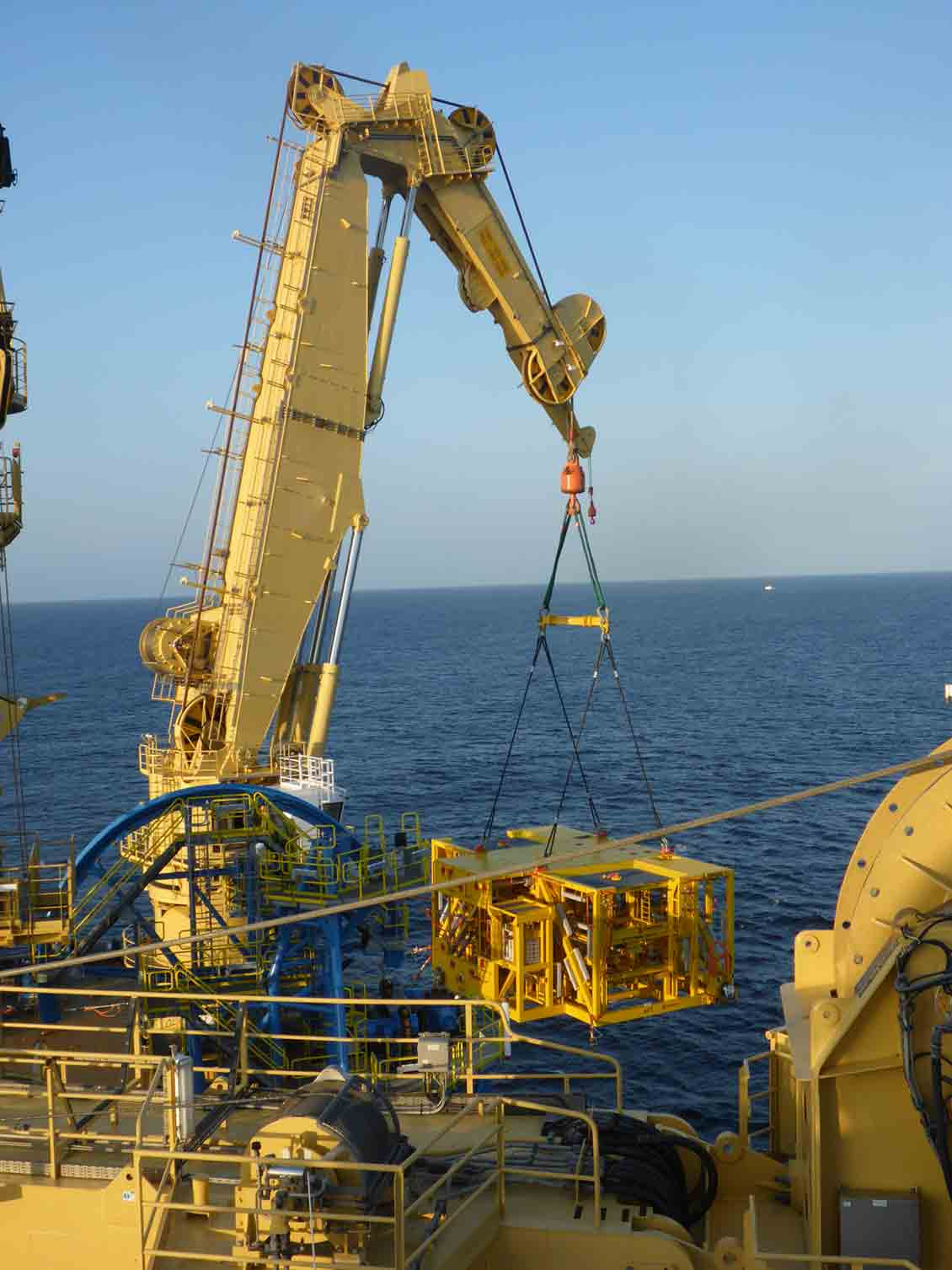 A crane lifting subsea equipment off of a platform and lowering it into the water.